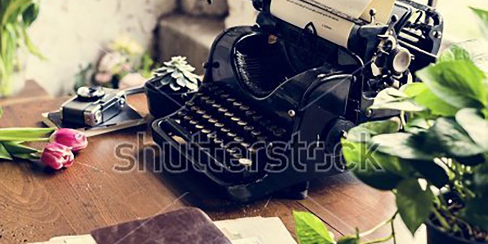 stock-photo-retro-typewriter-machine-old-style-by-tulips-flower-652594258